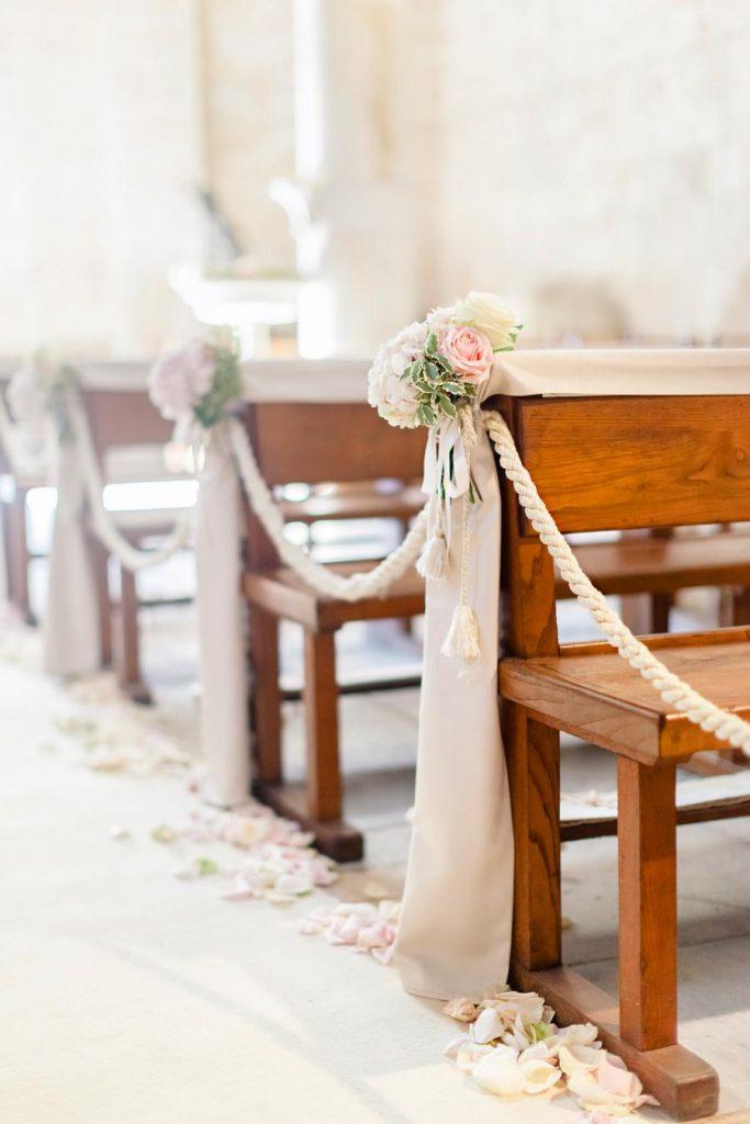 In questa foto addobbi chiesa per un matrimonio romantico ripresi da destra verso sinistra. I banchi sono decorati con drappi beige pendenti fino a a terra, mazzetti di fiori rosa e bianchi, legati da nappine beige. I banchi della chiesa sono infine collegate da un cordone beige. Lungo la navata sono sparsi petali di rosa bianchi