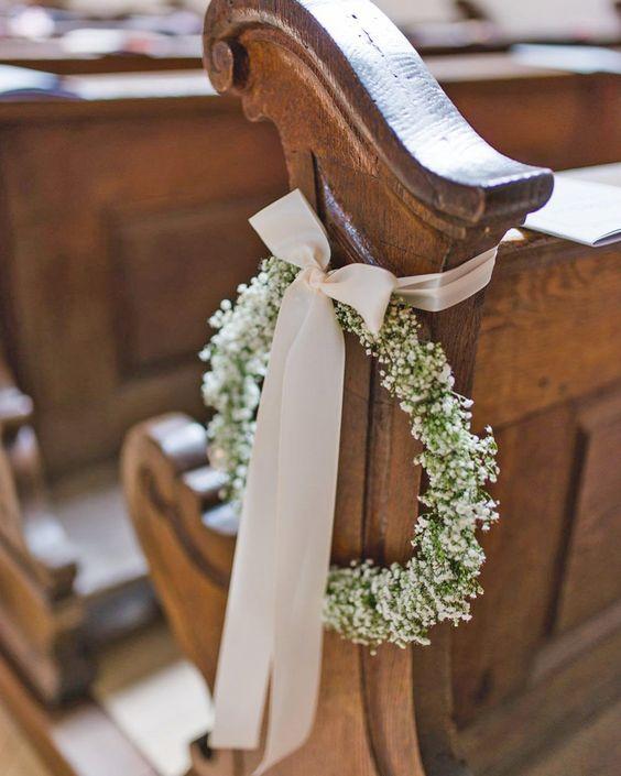 In questa foto il dettaglio di una decorazione per un matrimonio in chiesa. È un cerchio di nebbiolina legato con un nastro rosa cipria chiuso a fiocco