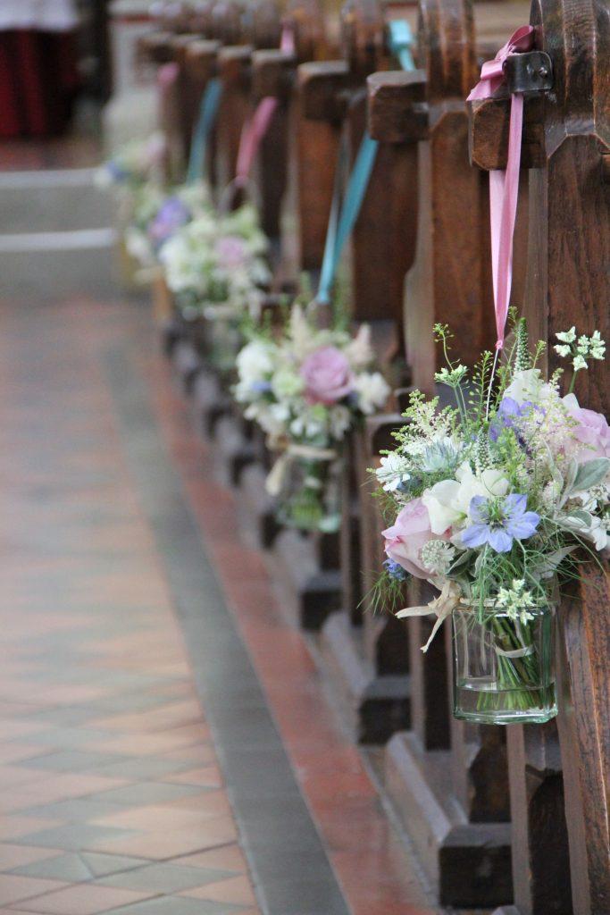In questa foto il dettaglio di addobbi per chiesa matrimonio shabby chic. Ai banchi sono legati con nastri, alternati, azzurri e rosa, vasetti di vetro trasparente riempiti di acqua e fiori di campo lilla e bianchi, rose rosa e nebbiolina