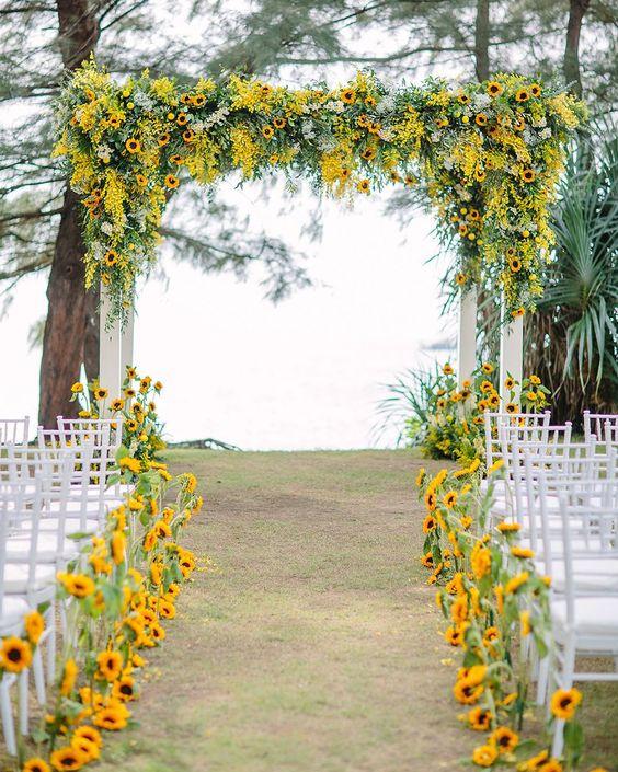 In questa foto l'allestimento di un matrimonio civile con girasoli sul gazebo e lungo il corridoio centrale