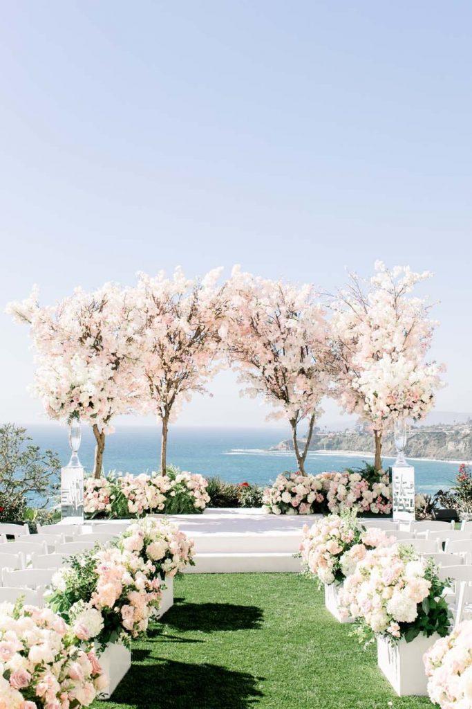 In questa foto l'allestimento per un matrimonio civile sul mare. Il prato è decorato con fiori bianchi e rosa mentre lo spazio dedicato al rito è circondato di alberi di ciliegio