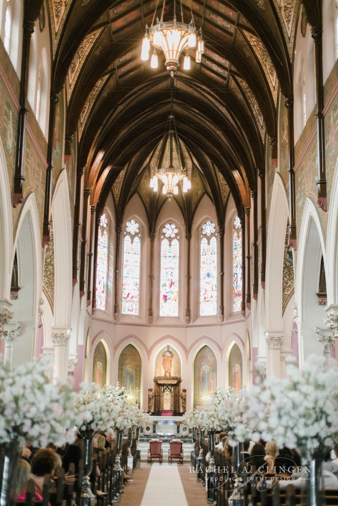 In questa foto una chiesa per matrimonio gotica con tetto in legno, colonne bianche e vetrate colorate. Lungo la navata sono disposti vasi alti e trasparenti con piccoli fiori bianchi e rosa. Alla fine della navata centrale si intravedono due poltrone rosa per gli sposi