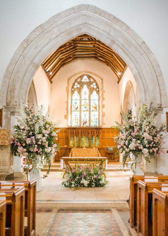 In questa foto l'altare di una chiesa per matrimonio con archi di marmo decorato con composizioni in vasi bianchi con fiori rosa e bianchi sistemate ai lati. In basso, davanti al tavolo della mensa, è adagiata un'altra composizione abbinata