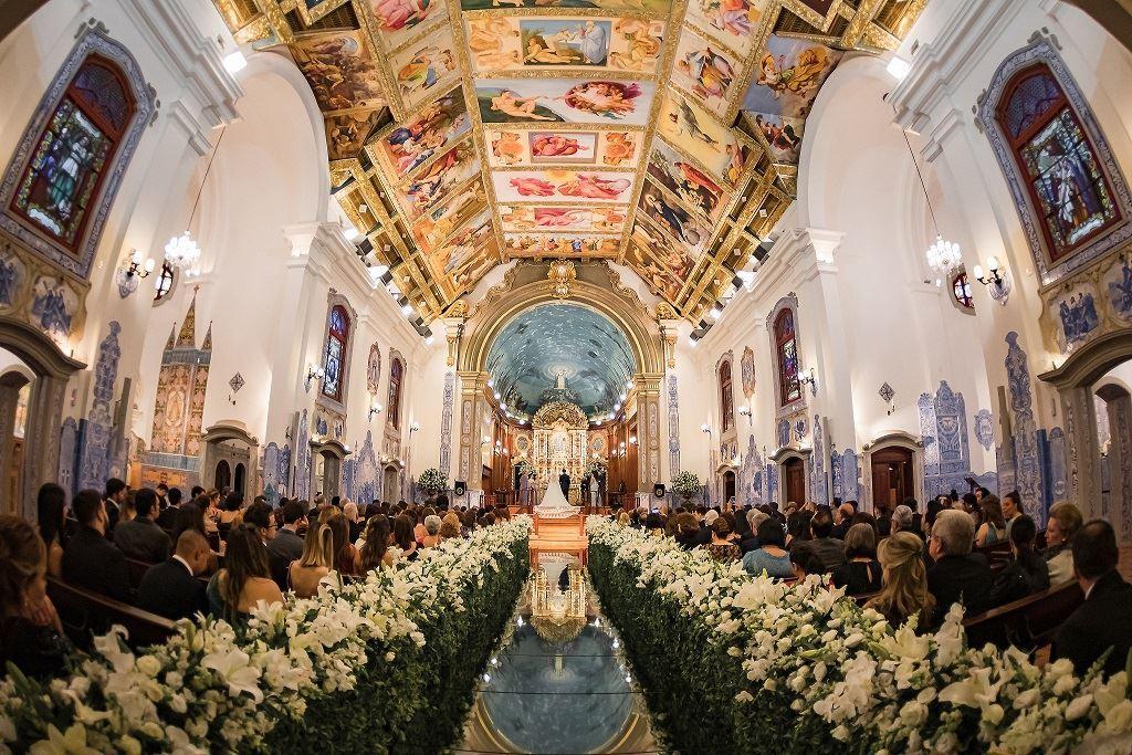 In questa foto una chiesa per matrimonio decorata con fiori bianchi lungo tutta la navata ricoperta da un tappeto riflettente. Ai lati sono seduti gli ospiti mentre sul fondo, all'altare, sono presente gli sposi in piedi. La chiesa presenta marmi grigi e azzurri lungo le pareti mentre il soffitto è ricoperto di dipinti e stucchi dorati. L'altare è coperto da una cupola azzurra