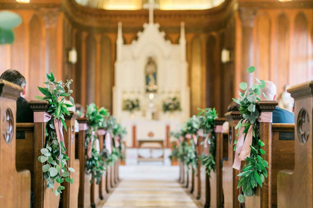 In questa foto una chiesa per matrimonio con pareti e banchi di legno decorati, a posti alternati, con mazzetti di eucalipto rivolti verso il basso fasciati da un nastro rosa cipria. Sullo sfondo si intravede l'altare bianco decorato con composizioni di foglie e fiori bianchi