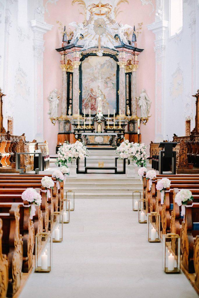 In questa foto una chiesa per matrimonio con pareti stuccate di bianco e altare rosa decorato con marmi neri e rosa e un grande dipinto dell'annunciazione. Ai banchi, a posti alternati, sono legati mazzetti di rose bianche, uguali a quelle usate per le decorazioni disposte sulla balaustra dell'altare. Lungo la navata, poggiate sul pavimento, sono disposti portacandele dorati a forma di parallelepipedo con all'interno candele grandi bianche accese