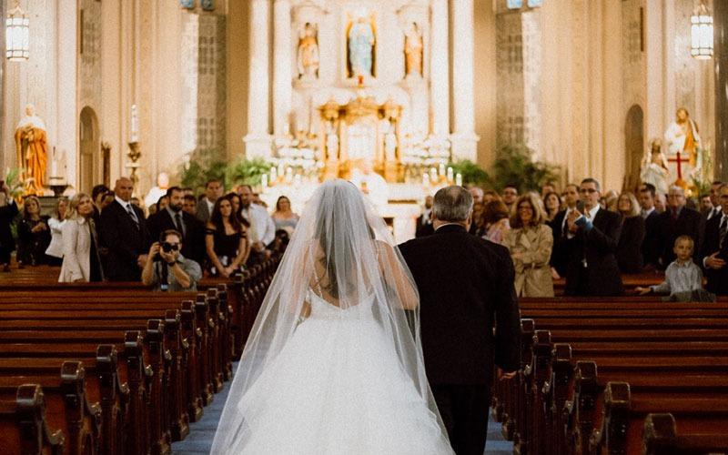 In questa foto una sposa entra in chiesa al braccio del padre e cammina lungo la navata di una chiesa illuminata mentre gli invitati, ripresi frontalmente, li guardano