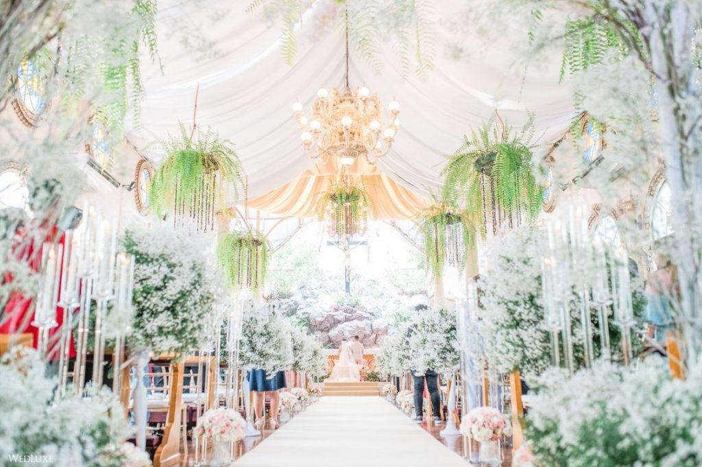 In questa una chiesa per matrimonio decorata con tende bianche sul soffitto e immersa in addobbi floreali di fiori bianchi lungo tutta la navata. Dal soffitto pendono composizioni di gelci. Sullo sfondo si intravedono gli sposi davanti ad un altare di pietra e un grande crocifisso che lo sovrasta