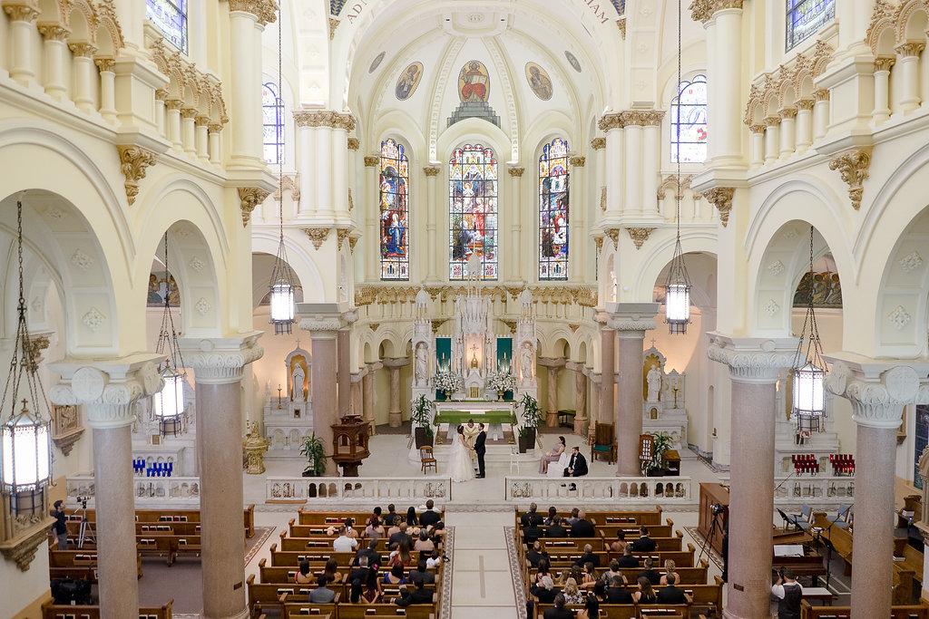 In questa foto una grande chiesa vista dall'alto durante un matrimonio. La chiesa è composta da archi bianchi, colonne di marmo rosa e una grande cupola sopra l'altare. Sulla cupola sono presenti vetrate colorate con scente di santi, sovrastate da altri dipinti. All'altare ci sono due sposi in piedi l'uno di fronte all'altra si tengono per mano davanti al sacerdote. L'altare è separato da una balaustra di marmo. Ai banchi sono seduti gli ospiti