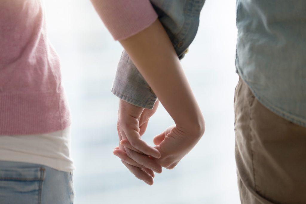 In questa foto le mani di un uomo e una donna strette l'una nell'altra