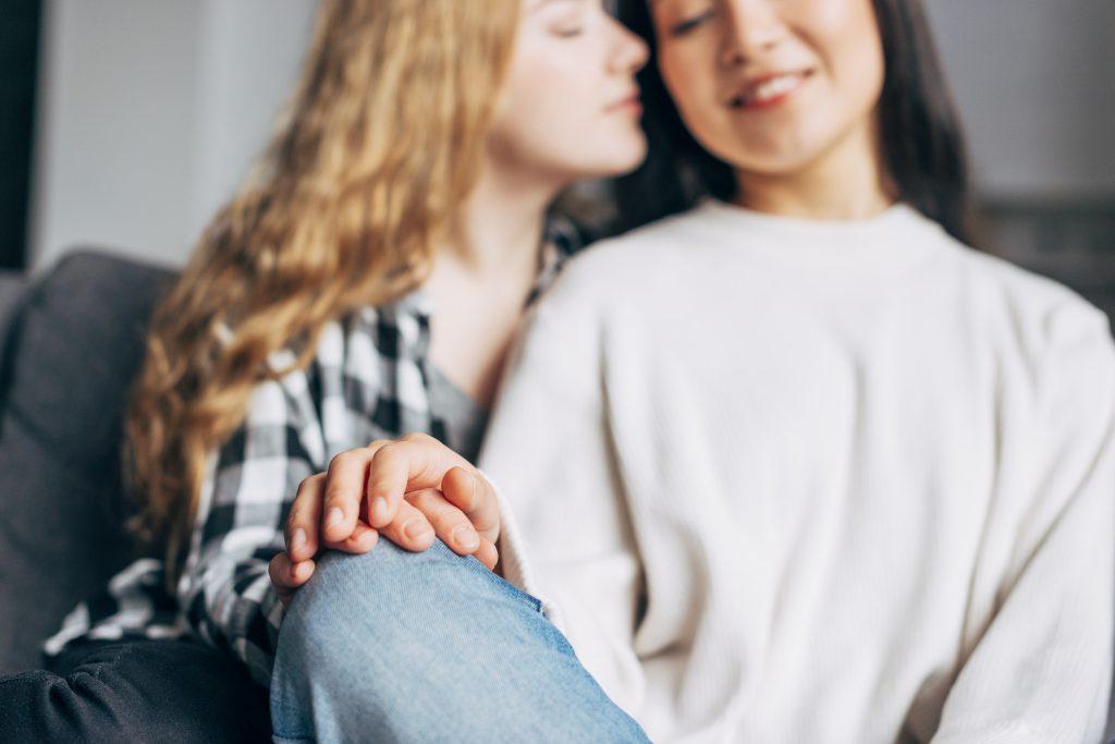 In questa foto due ragazze sul divano si stringono le mani poggiate sulle gambe. La ragazza a sinistra si avvicina all'altra come per baciarla sulla guancia