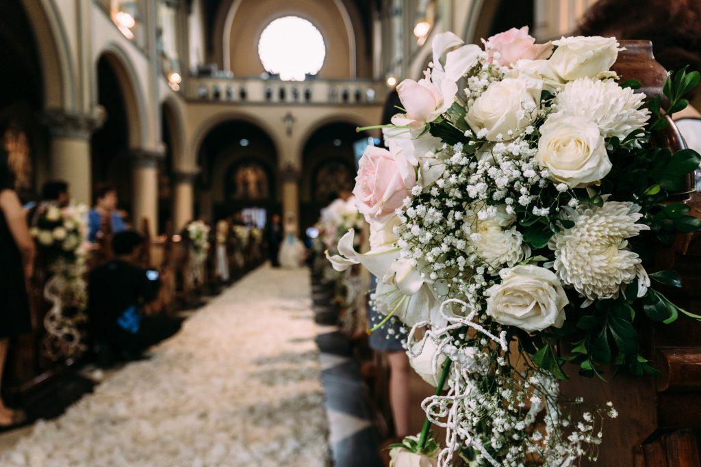 In questa foto una composizione floreale che decora uno dei banchi dei una chiesa per matrimonio. È realizzata con rose bianche e rpsa, nebbiolina e foglie