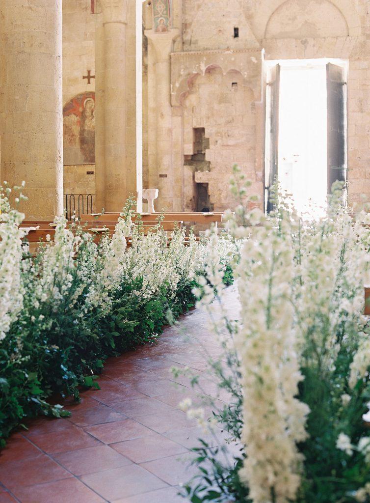 In questa foto una chiesa rustica con pareti e colonne in pietra, decorata per un matrimonio. La navata centrale è interamente ricoperta sui lati di composizioni di foglie e gladioli bianchi