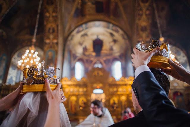 In questa foto due sposi di spalle durante l'incoronazione del loro matrimonio religioso. Sono mostrate solo le teste mentre due persone poggiano le corone
