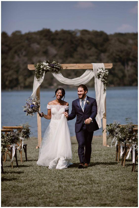 In questa foto due sposi felici e sorridenti si allontanano dalla location del rito civile su un prato sulla riva di un lago. In fondo si intravede l'arco nuziale decorato con un drappo di stoffa bianca e fiori di lavanda, usati anche nel bouquet della sposa e nelle decorazioni delle sedie