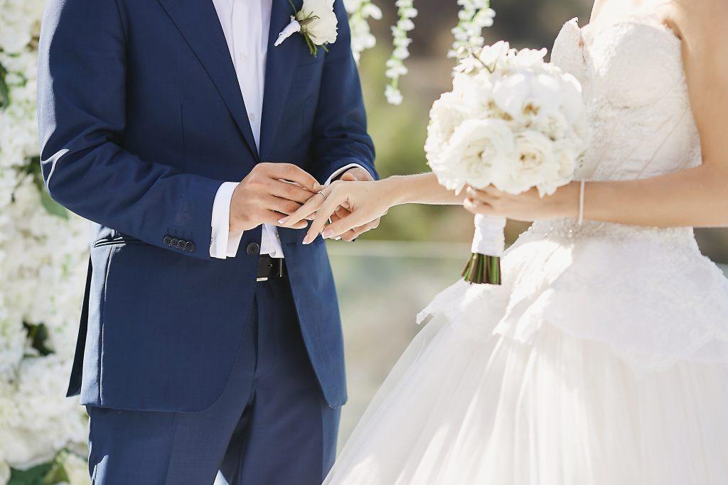 In questa foto uno sposo mette la fede al dito della sposa