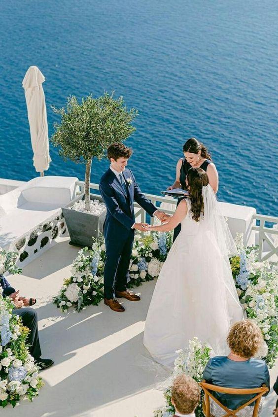 In questa foto due sposi si tengono per mano mentre una loro amica celebra il matrimonio civile su una terrazza sul mare della Grecia, decorata con rose bianche e ortensie azzurre