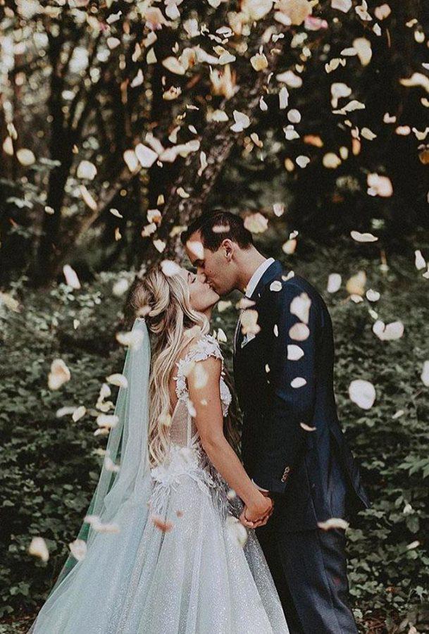 In questa foto due sposi si baciano in un giardino sotto una cascata di petali di rossa rosa. Lei indossa un velo da sposa verde menta