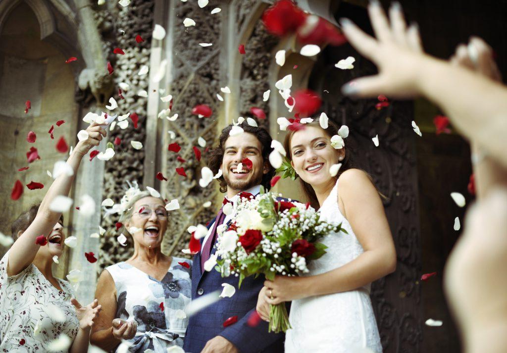 In questa foto due sposi sorridenti escono dalla chiesa mentre gli invitati lanciano riso e petali di rose rosse e bianche