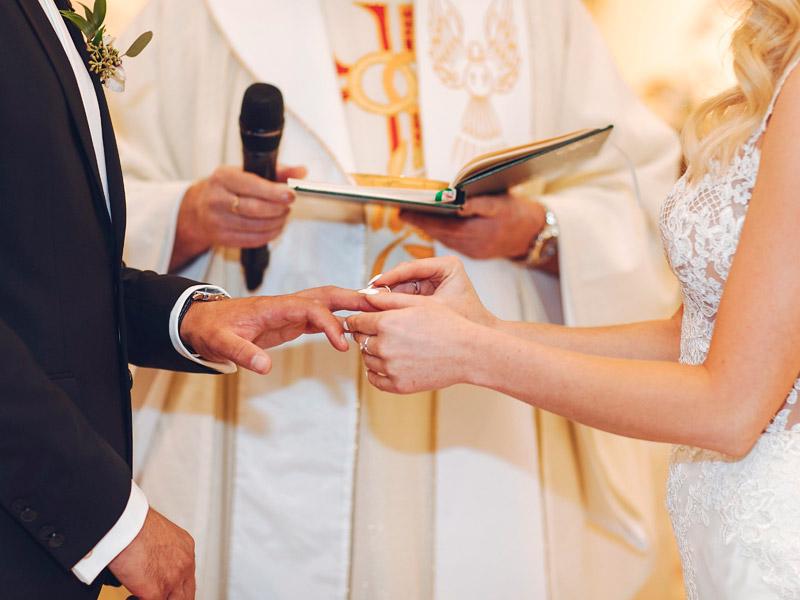 In questa foto due sposi si scambiano le fedi davanti al sacerdote. Sono riprese soltanto le mani. La sposa mette la fede al dito dello sposo mentre il sacerdote regge il libro con le promesse nella mano sinistra e il microfono nella mano destra