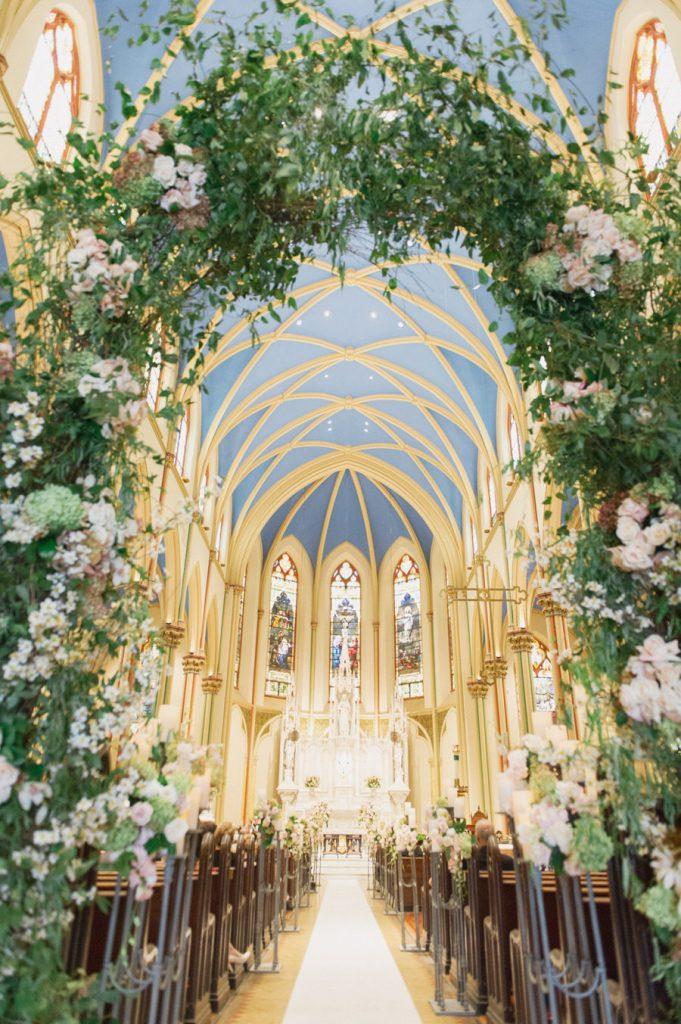 In questa foto una chiesa decorata per un matrimonio religioso. In primo piano è presente un grande arco di foglie e fiori rosa e bianchi. Gli stessi fiori decorano i banchi della chiesa. Dall'arco di fiori si intravede il tetto ad archi azzurro e l'altare con vetrate a mosaico in stile gotico