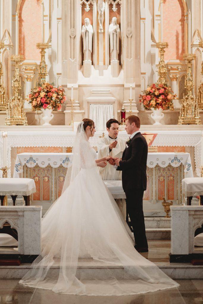 In questa foto due sposi si guardano e si tengono le mani mentre si scambiano le fedi in chiesa durante il loro matrimonio religioso. Il sacerdote regge il microfono allo sposo ripetendo le promesse. In primo piano è mostrato il velo disteso tra lo spazio dell'altare e il marmo della navata centrale. Dietro di loro un altare di marmo rosa e bianco