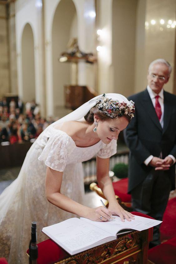 In questa foto una sposa ripresa frontalmente mentre, chinata, firma i documenti del matrimonio in chiesa. In primo piano si vede una folta corona di fiori di campo che circonda l'attaccatura del velo. Indossa una abito con ricami floreali e manichette sulle spalle. La guarda il suo papà dietro di lei con le mani giunte