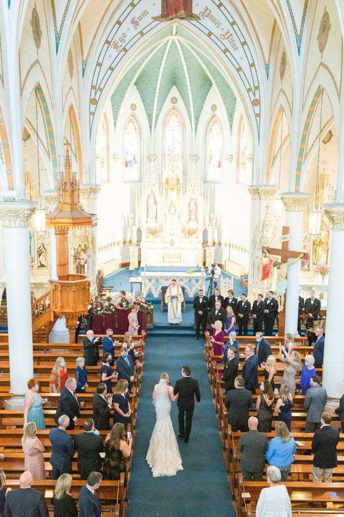 In questa foto l'ingresso della sposa in chiesa al braccio del padre, ripreso dall'alto. Sposa, papà ed ospiti ai banchi sono ripresi di spalle. Ad aspettarli all'altare il sacerdote che celebrerà la messa, i testimoni e le damigelle in abito bordeaux. La navata è ricoperta da un tappeto blu navy