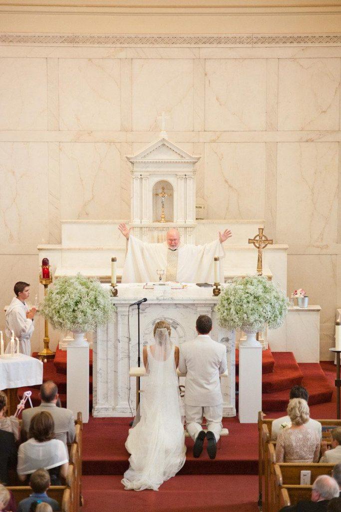 In questa foto due sposi inginocchiati all'altare davanti al sacerdote che li benedice a braccia aperte