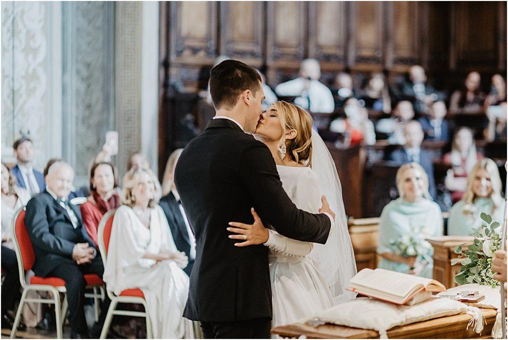 In questa foto due sposi si baciano alla fine della celebrazione del loro matrimonio nella Basilica di San Pietro. Dietro di loro si intravedono gli ospiti che li guardano sorridenti