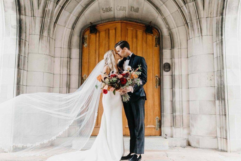 In questa foto due sposi si baciano davanti alla porta di una chiesa gotica in marmo e legno. Il velo della sposa svolazza. Entrambi gli sposi tengono tra le mani il bouquet di fiori rossi, rosa, gialli e foglie verdi