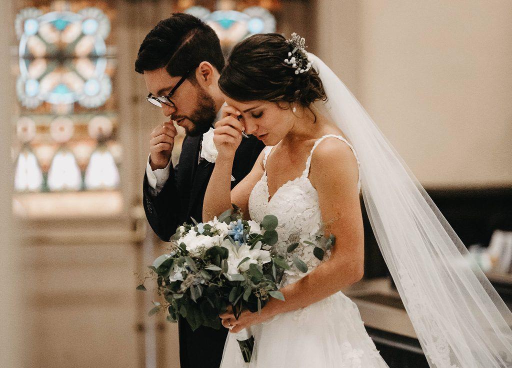 In questa foto due sposi si fanno il segno della Croce durante una preghiera del loro matrimonio in chiesa. Entrambi gli sposi hanno gli occhi chiusi e la testa abbassata. In primo piano è mostrato il bouquet di alloro, fiori bianchi e blu.