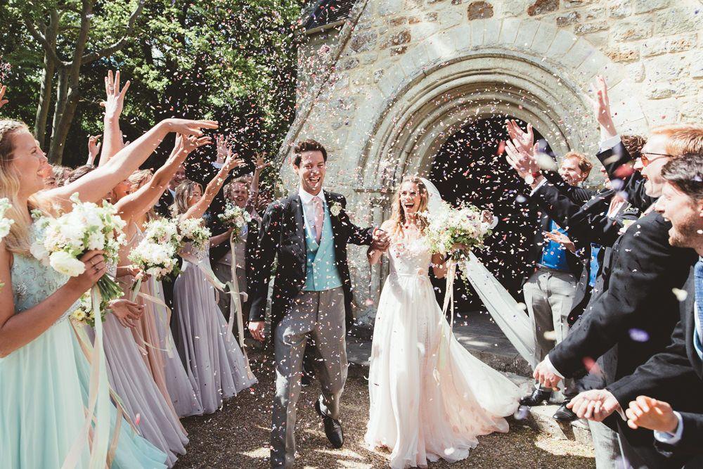 In questa foto due sposi felici escono dalla chiesa dove è stato celebrato il loro matrimonio mentre gli ospiti lanciano riso bianco e fuxia. Alla sinistra sono inquadrate le damigelle in abiti lilla e verde acqua. Sul lato destro sono presenti i testimoni. Lo sposo indossa un tight nero con panciotto azzurro e cravatta rosa