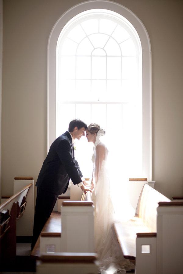 In questa foto due sposi in una chiesa  vuota prima del loro matrimonio si guardano poggiando la fronte uno sull'altra al di là di uno dei banchi di fronte ad una finestra da cui filtra la luce del giorno