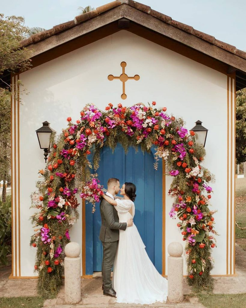 In questa foto due sposi si abbracciano sfiorandosi i nasi davanti alla piccola cappella delle loro nozze religiose con una porta azzurra decorata con un arco di fiori rossi, fuxia e rosa e foglie di felce. Ai lati si intravedono due lampioni