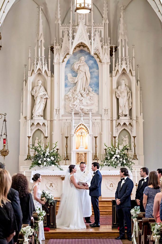 In questo articolo due sposi si tengono per mano all'altare durante la celebrazione del loro matrimonio religioso. Il sacerdote recita la benedizione mentre tutti gli ospiti assistono alla cerimonia. La chiesa è decorata con statue di marmo bianco all'altare e con fiori bianchi lungo la navata e all'altare