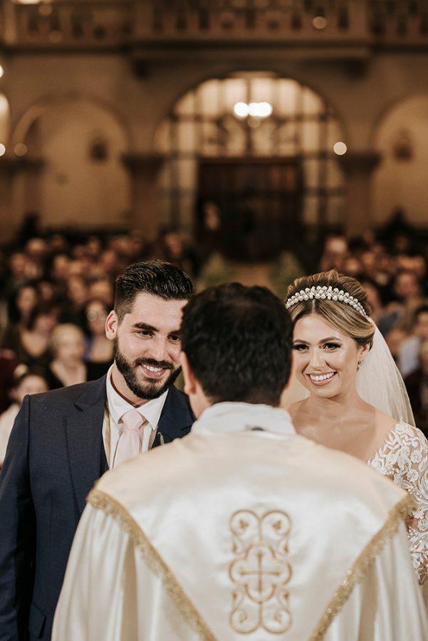 In questa foto due sposi sorridono al sacerdote del loro matrimonio in chiesa e ripreso di spalle