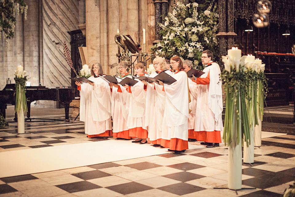 In questa foto un coro canta in una chiesa gotica durante un matrimonio religioso. I membri del coro indossa una tunica rossa e bianca e tengono il libro dei canti aperto sulle mani. La chiesa è decorata con candele e composizioni di fiori bianchi
