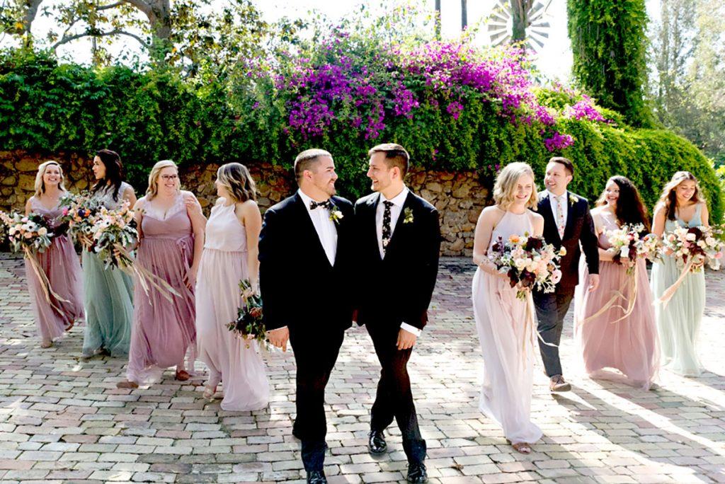 In questa foto due sposi gay si guardano e si tengono per mano circondati sui lati, ma disposti in obliquo, dalle damigelle con abiti colore rosa cipria, malva e verde menta e da un testimone