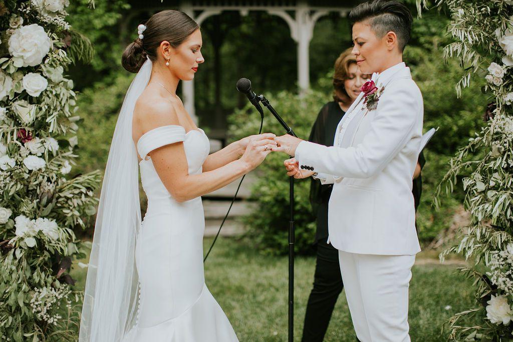 In questa foto due spose durante la cerimonia del loro matrimonio gay. La sposa sulla sinistra in abito bianco e velo mette la fede al dito della sua compagna in smoking bianco mentre l'ufficiale di stato civile legge le promesse