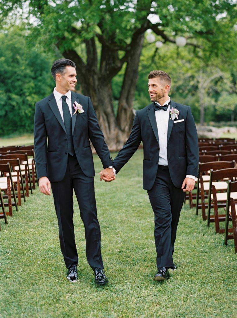 In questa foto due sposi gay escono mano nella mano dalla location della loro unione civile su un prato. Si guardano sorridenti