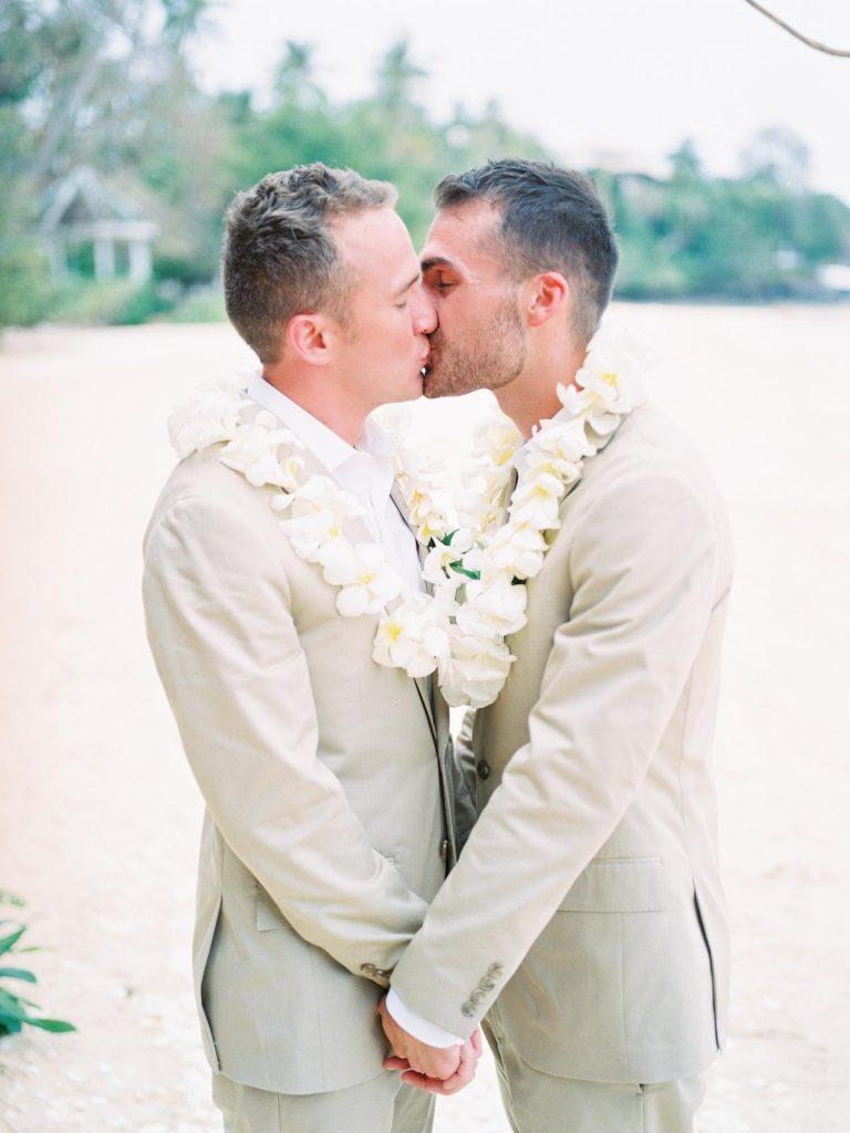 In questa foto due sposi gay si baciano e si tengono per mano sulla spiaggia dopo la loro unione civile. Indossa due abiti beige con camicie bianche e collane di fiori bianchi. Sullo sfondo si intravede una foresta tropicale