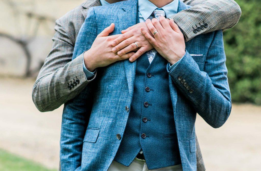 In questa foto due uomini ripresi da collo al busto si abbracciano uno di spalle all'altro. Lo sposo posizionato davanti indossa un abito azzurro mentre lo sposo che lo abbraccia da dietro indossa un abito grigio. Mostrano entrambi le fedi