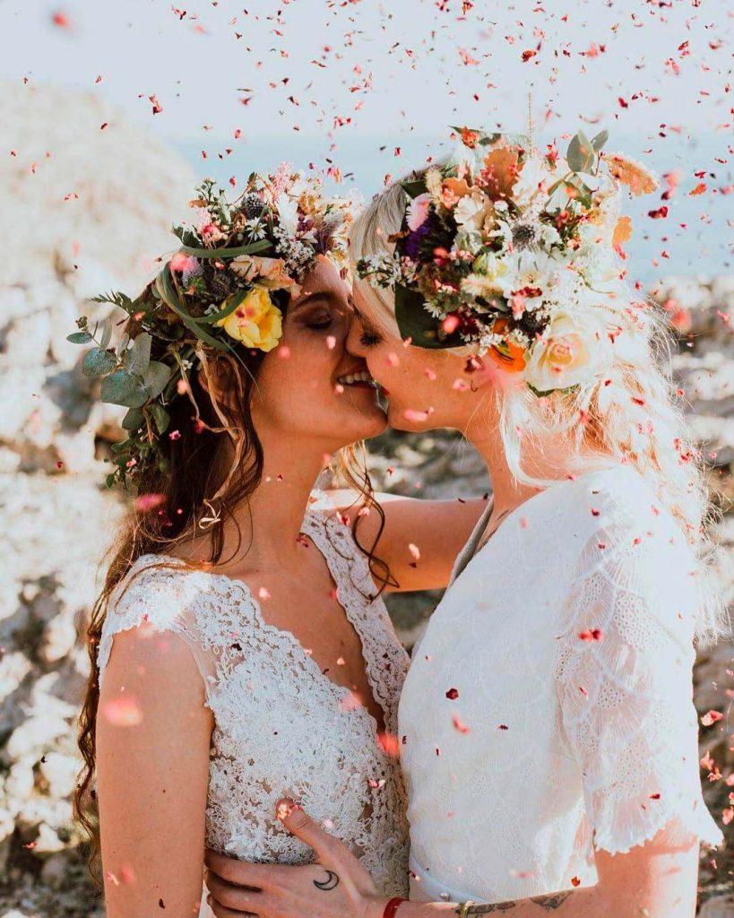 In questa foto due spose si abbracciano e si baciano tra coriandoli rosa e rossi. La sposa a sinistra indossa un abito in pizzo con spalline larghe, la sposa a destra un abito con maniche a tre quarti. Entrambe indossa una corona di fiori gialli, rosa e bordeaux e foglie di alloro