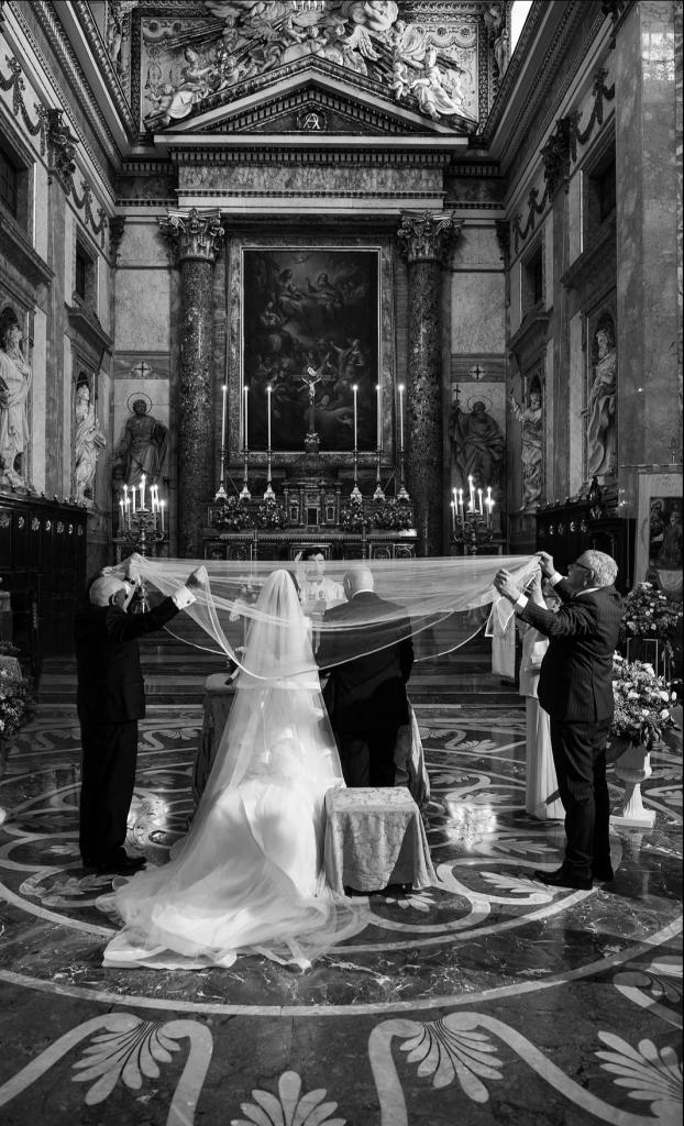 In questa foto in bianco e nero due sposi di spalle durante il rito della velazione. Sopra le loro teste è disteso un velo tenuto agli angoli dai quattro genitori