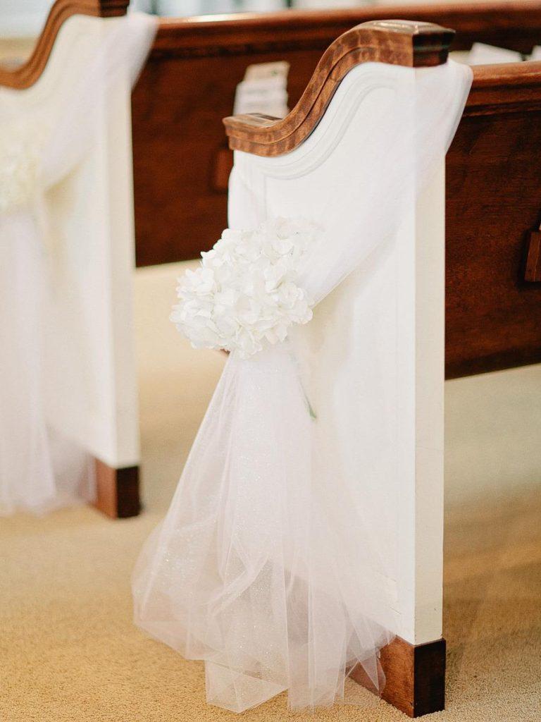 In questa foto un velo circonda il banco di una chiesa per le nozze ed è fermato da un piccolo bouquet di fiori bianchi