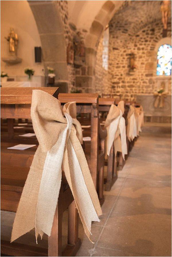 In questa foto una chiesa semplice decorata con fiocchi di juta bianca e beige legati ai banchi