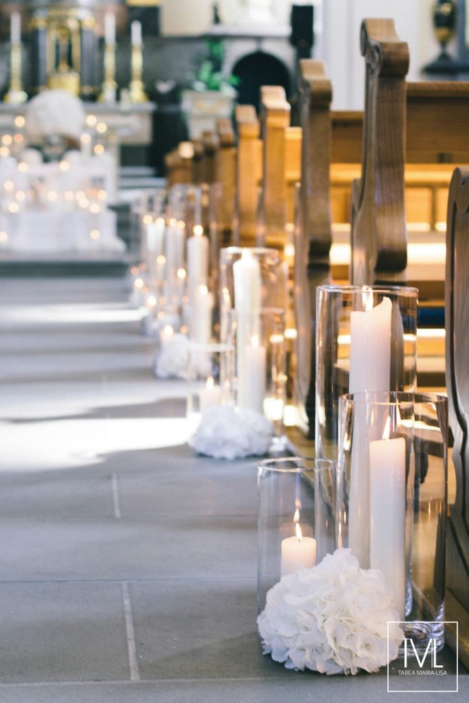In questa foto una chiesa decorata lungo la navata con candele poggiate sul pavimento e accese in cilindri trasparenti e sfere di fiori bianchi