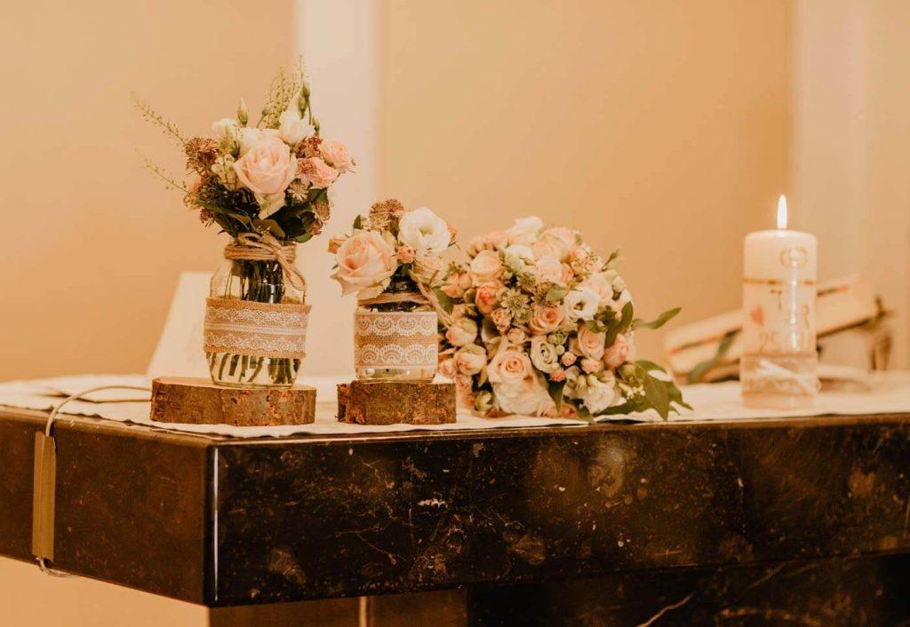 In questa foto una mensa della chiesa decorata in stile shabby chic con vasi di vetro decorati con nastri di juta e pizzo poggiati su cilindri di legno. I fiori scelti sono rose bianche e rosa