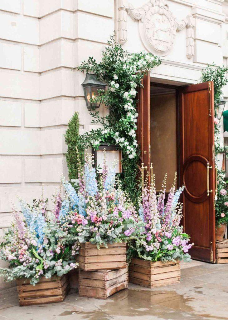 In questa foto l'esterno di una chiesa decorata con cassette di legno piene di gladioli colore azzurro, lilla, rosa e foglioline verdi